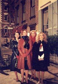 4 women in coats on street