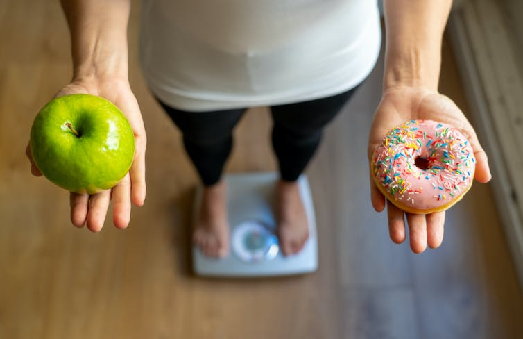 A person stands on the scales, holding an apple in one hand, and a donut in the other.