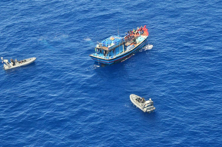 A Vietnamese illegal fishing vessel in the Coral Sea being intercepted by border force boats