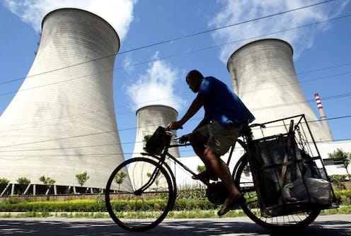 Man rides bike past coal plant