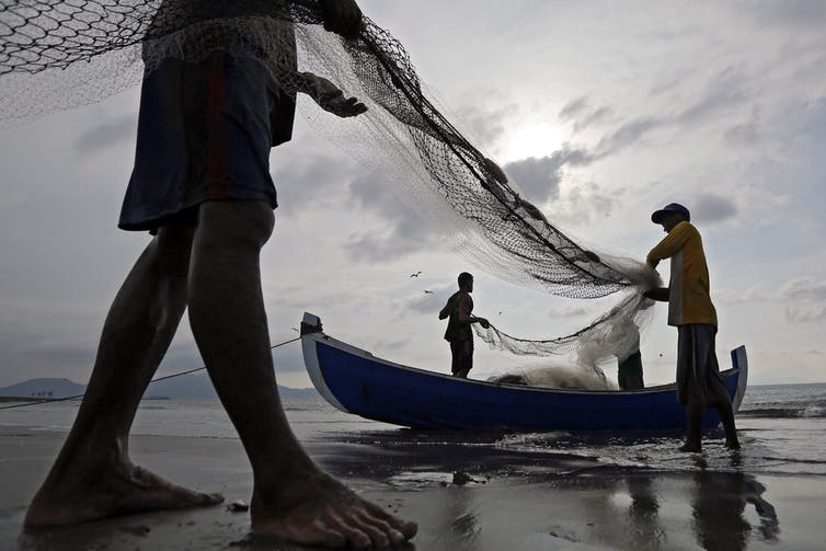 Three men haul fishing nets by a small boat at a beach.