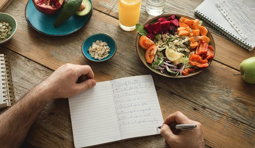 A man writes in a diary on a table with healthy food.