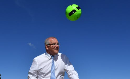 Australian prime minister Scott Morrison plays with a ball.