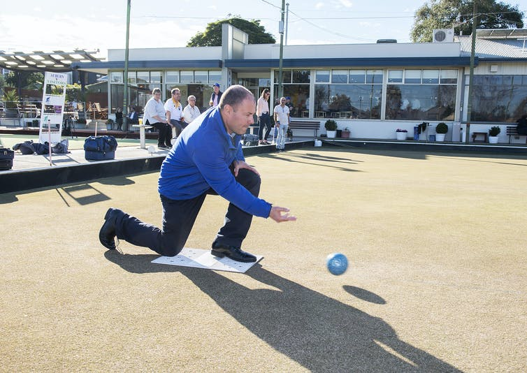 Treasurer Josh Frydenberg rolls a ball.