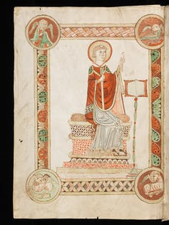 An illustration from an illuminated manuscript showing Bede as a saint writing.