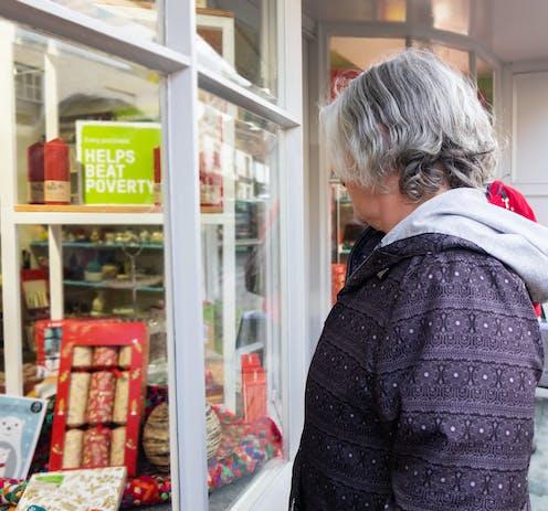 Older woman with in purple jacket looking in charity shop window
