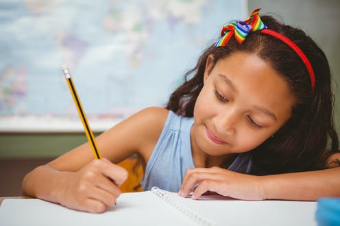 Girl writing in notebook with pencil