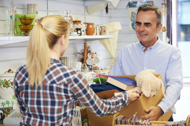 Man handing blonde woman box of donations in charity shop
