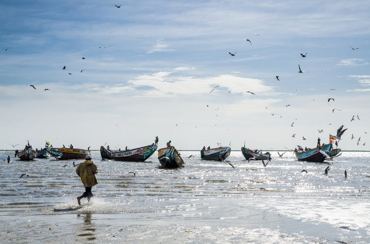 Local fishing boats sit off the shore with man running past