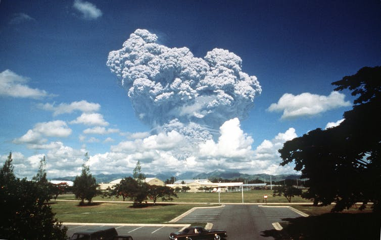 A large volcanic eruption cloud seen from distance.