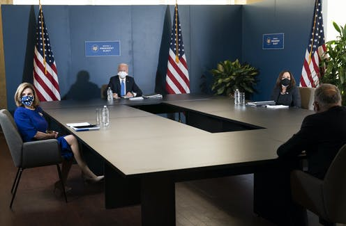 Joe Biden, Kamala Harris, Chuck Schumer and Nancy Pelosi sit far apart at a table.