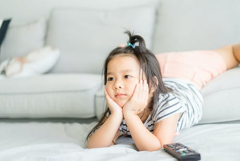 A young girl watches television with a remote on the ground next to her