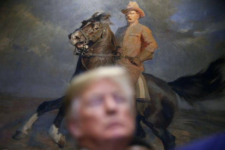 Donald Trump stands in front of a painting of former President Teddy Roosevelt in the White House.