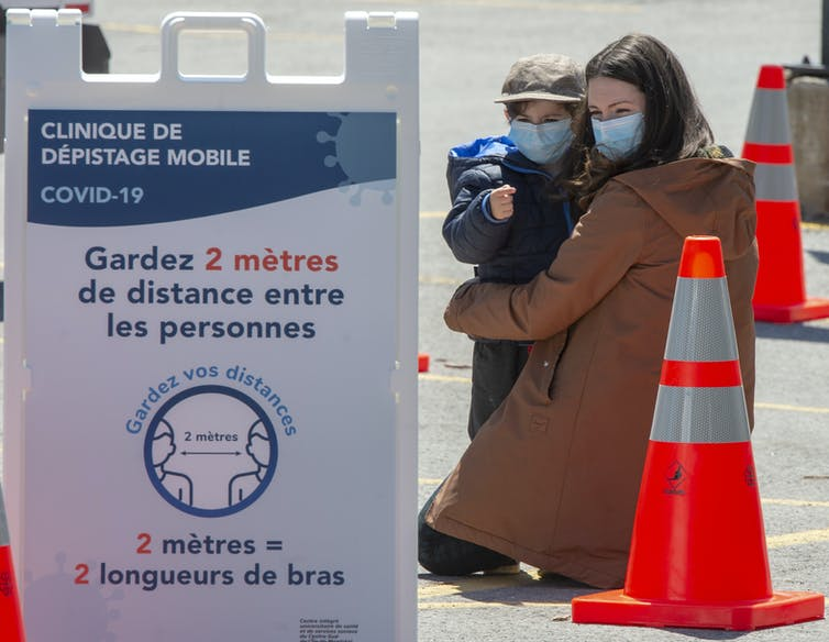 A woman in a face mask hugs her child, also in a face mask, in a parking lot behind a sign for COVID-19 testing.