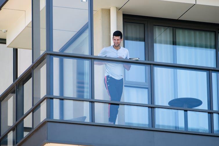 Tennis player Novak Djokovic leans on a glass balcony.