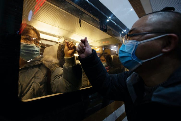 A man and a woman, both wearing surgical masks, place their hands on a glass window that separates them.