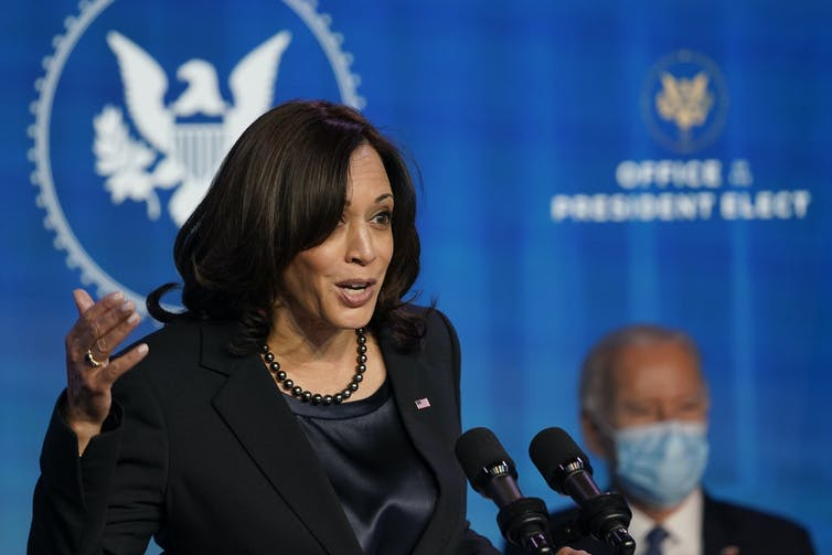 Kamala Harris delivers a speech. Joe Biden is sitting in the background.