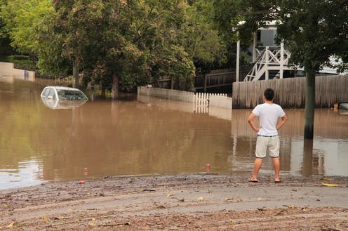 A man looks at floodwaters.