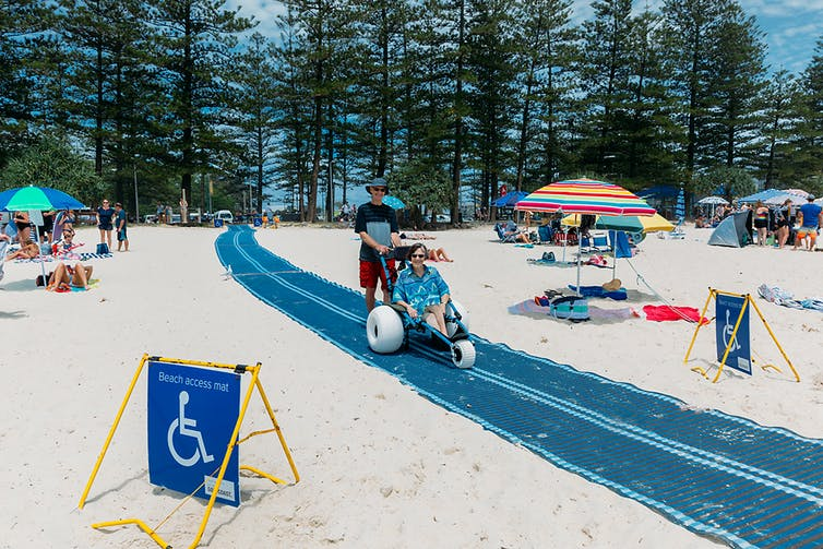 A blue mat cuts across the white sandy beach. A woman smiles in a beach wheelchair.