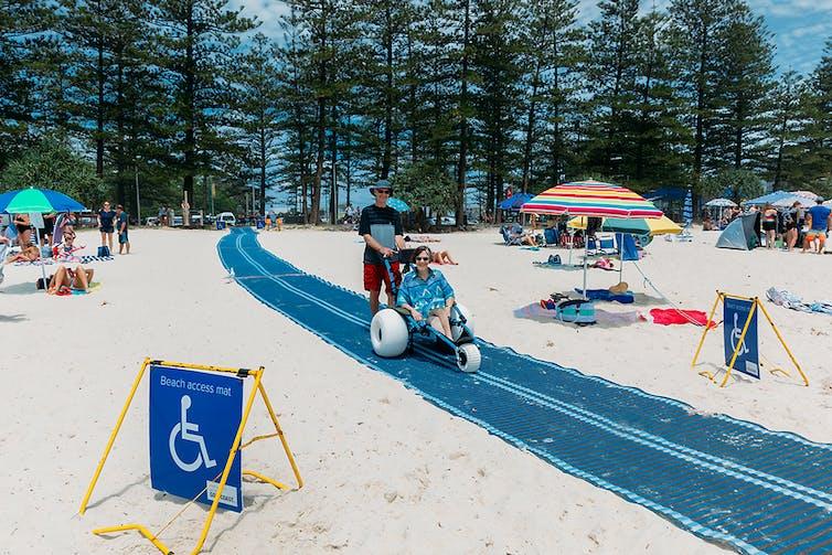 A blue mat cuts across the white sandy beach. A woman smiles in a beach wheelchair.