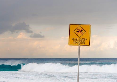 A beach sign reads: beach closed. Dangerous conditions.