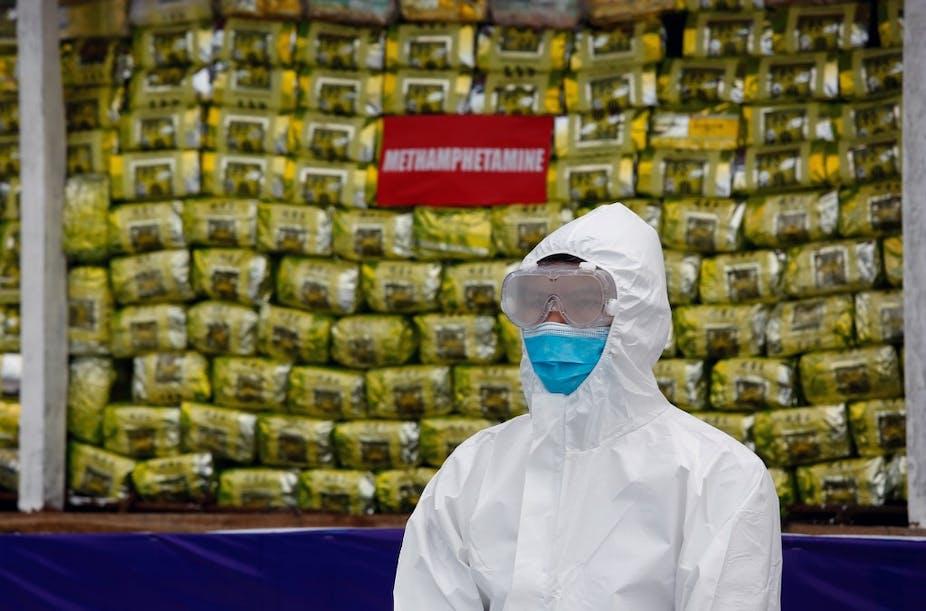Un policier se tient devant une pile de drogue lors d'une cérémonie de destruction