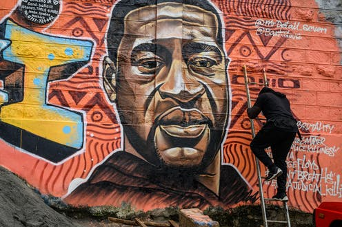 A mural artist climbs up a ladder leaning against a wall that features a mural of a black man, eyes cast downward.