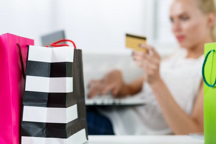 Blond woman making purchasing via internet paying credit card. Focus on fresh buying packed in colored paper bags standing in front of her. Shopping, consumerism, delivery and present concept