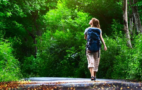 A woman in a backpack walking through a forest
