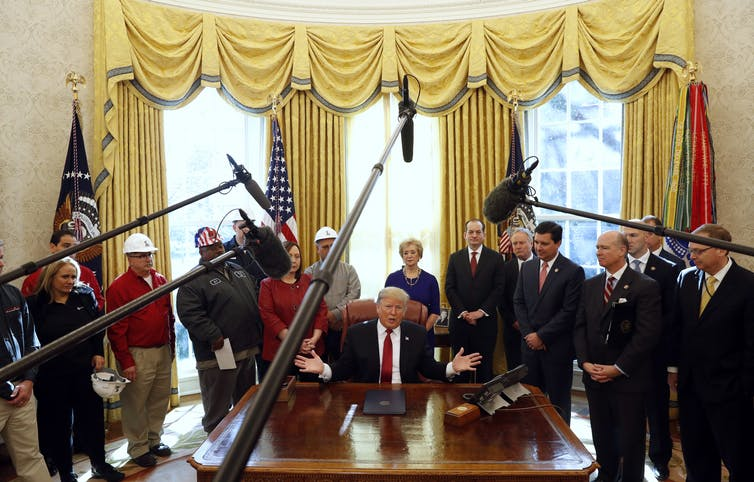 Trump is surrounded by manufacturers and media cameras in the Oval Office.