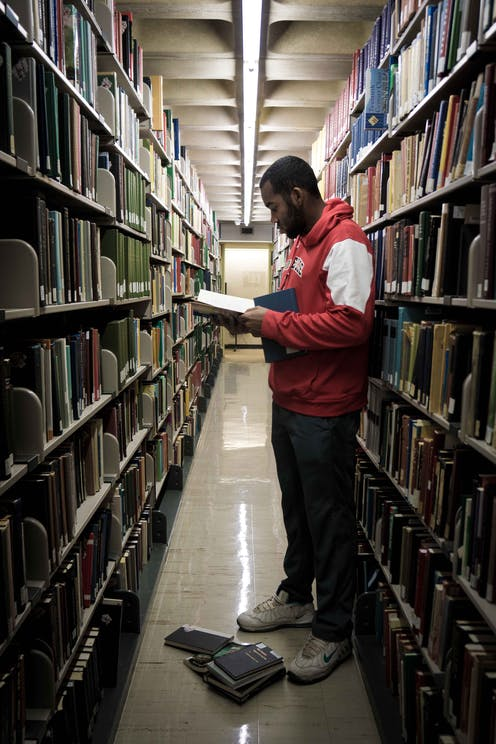 Man stands between two tall shelves of books