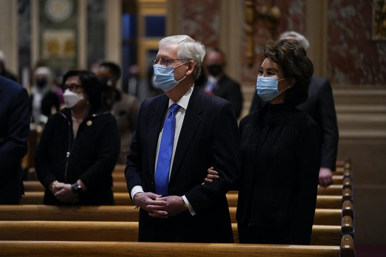 Senate Minority Leader Mitch McConnell and his wife Elaine Chao, in masks, stand behind a church pew.
