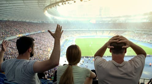 Three fans watching a football match.