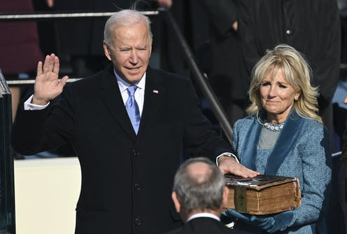 Biden takes the presidential oath of office, his hand on a Bible.