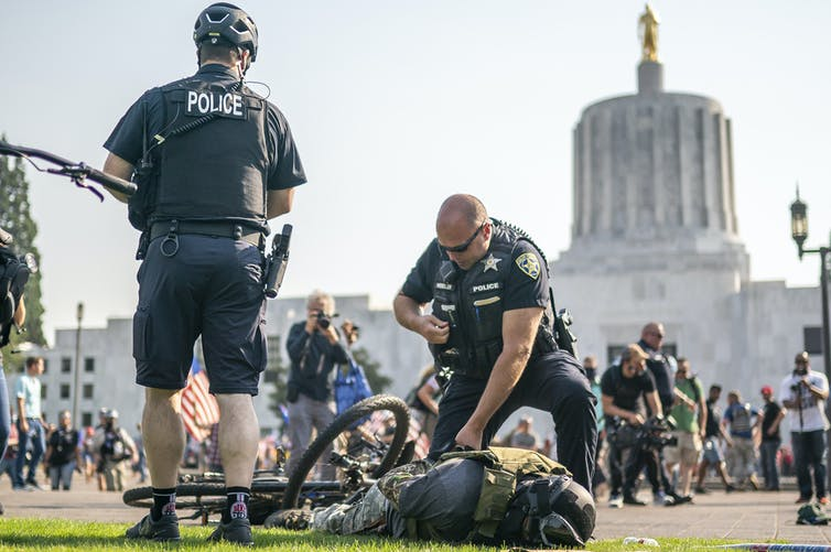 Man in militia gear lies face down on the ground in handcuffs with police standing over
