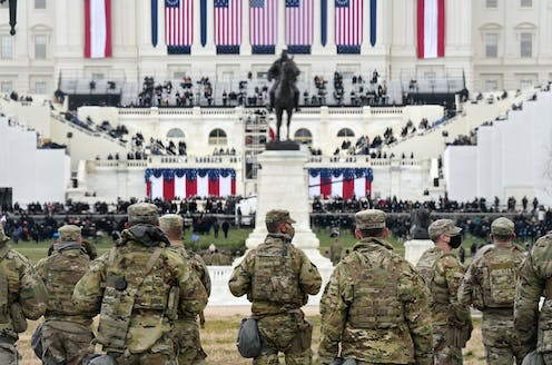 Members of the National Guard gather near the U.S. Capitol, with Biden's inaugural preparations visible in background