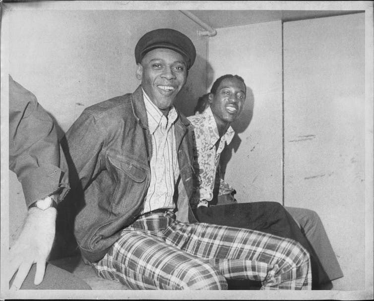 Two Black men in handcuffs in a paddy wagon smile at the camera