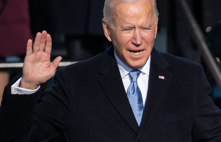 Joe Biden holds up his hand while swearing the Oath of Office during his inauguration on January 20, 2021.
