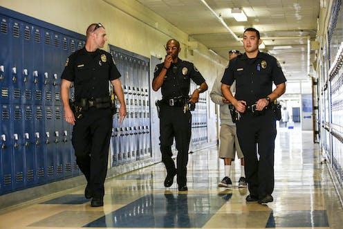 Three police officers walk down a school hallway.
