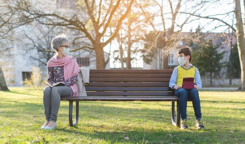 A woman and her grandson wearing face masks sitting on opposite ends of a park bench