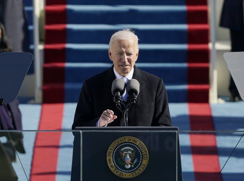 Joe Biden standing at a lectern outside the US Capitol to deliver his inaugural speech, January 20, 2021