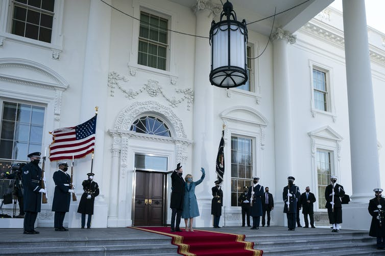 President Joe Biden and first lady Jill Biden wave as they arrive at the North Portico of the White House on Jan. 20.
