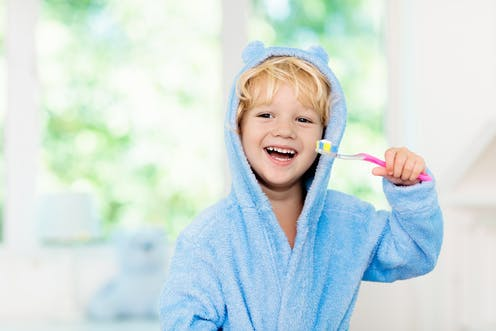 A young boy in his dressing gown smiling and holding a toothbrush.