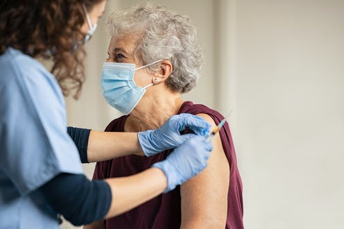 Older woman getting a vaccine.
