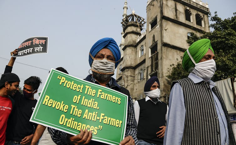 A protester hold a sign that reads: protect the farmers of India, revoke the anti-farmer ordinances.