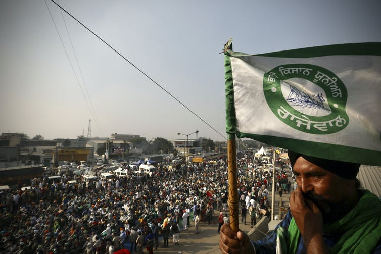 A man carries a flag. Behind him a crowd of protesters march along a road.