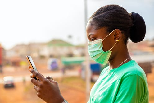 A surgical in a green surgical mask holding a mobile phone