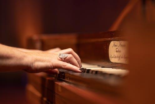 Hands play antique piano keys
