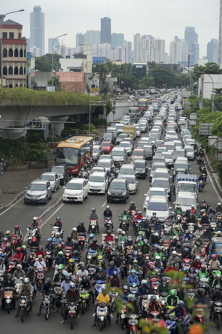 Ratusan mobil dan motor berhenti di depan lampu merah.