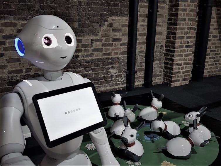 A white robot with a screen on its chest stands in front of rabbit bots.